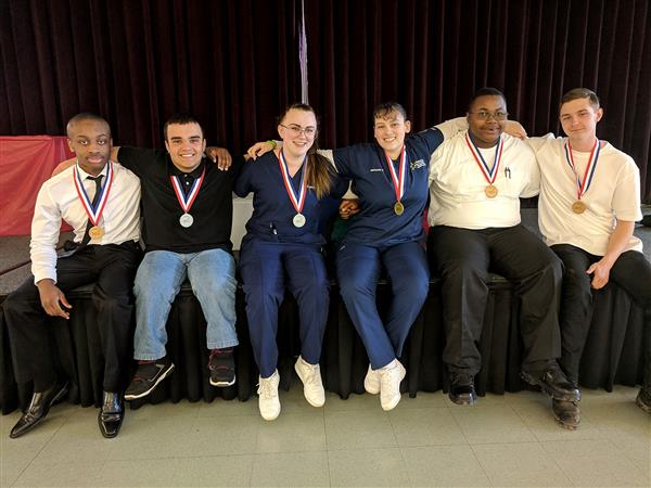 Six students sitting with their medals