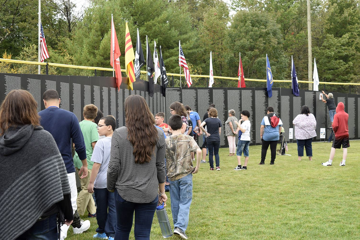 students looking at the names on the wall